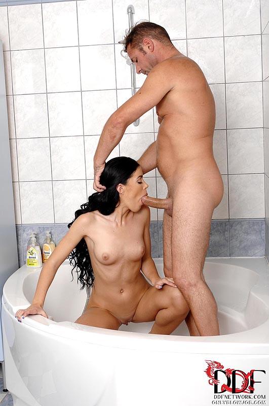 Кудрявая брюнеточка берет в рот у юношу постарше под душем
