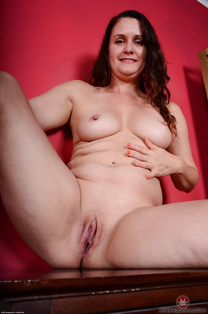 Опытная темненькая девушка выставляет напоказ побритую вагину сидя на комоде